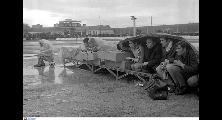 Χαρακτηριστική εικόνα από τον αγώνα ανάμεσα ΑΕΚ και Παναχαϊκή τον Φεβρουάριο του 1972, με τους αναπληρωματικούς να προσπαθούν να καλυφθούν από τη βροχή με κάθε δυνατό μέσο. Διακρίνονται: ο Στέλιος Σεραφείδης καθισμένος πάνω στην μπάλα, ο Μπάμπης Ψυμόγιαννος και ο  Λευτέρης Ιστόριος ξαπλωμένοι στα στρώματα και οι Ανδρέας Παπαεμμανουήλ, Σταμάτης Παπασταματίου (έφορος) Γιώργος Κάχρης και Κοκκινίδης (φροντιστής) κάτω από το πρόχειρο κάλυμμα.